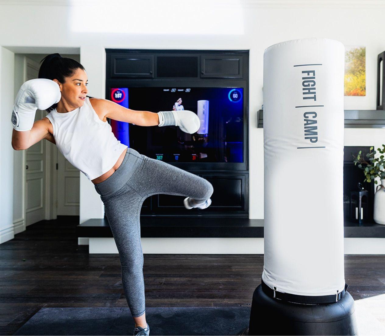 Woman kicking free standing punching bag