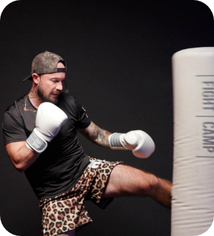 Trainer Aaron Swenson kicking the free standing bag with leopard print shorts