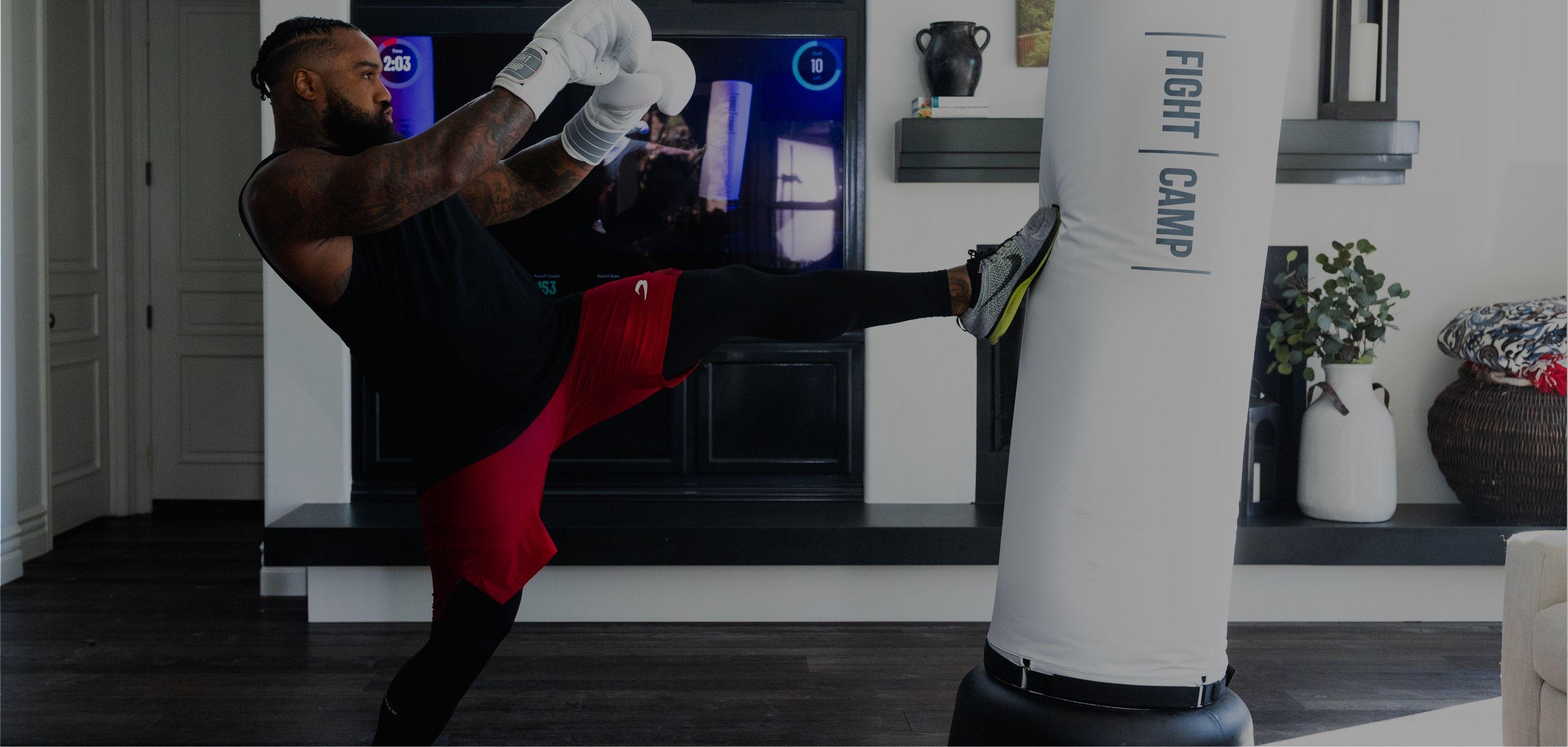 Man kicking free standing punching bag kickboxing